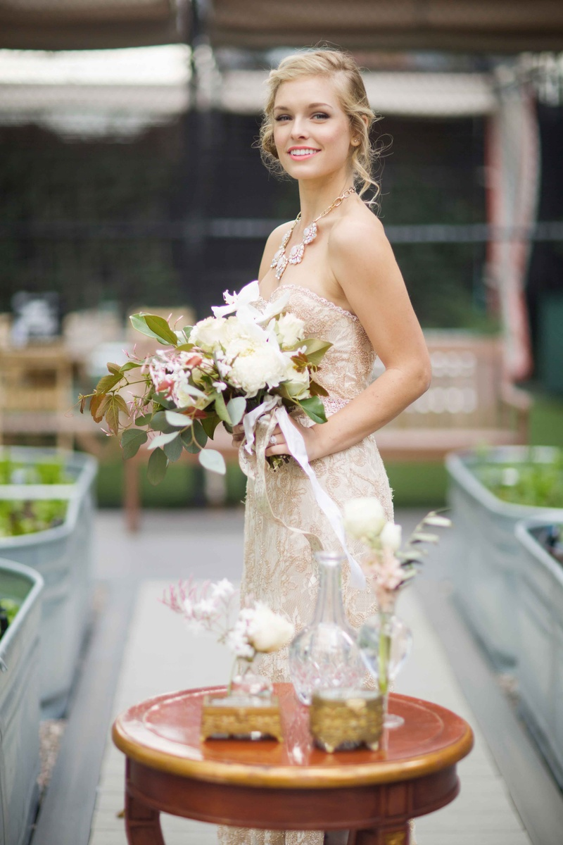 bride in champagne gown, pink lipstick, bouquet with lots of foliage