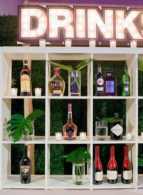 wedding bar white bookcase bookshelf alcohol bottles monstera leaves marquee sign