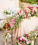 sweetheart table with blush linen pink orange flowers greenery gold lanterns white settee for couple