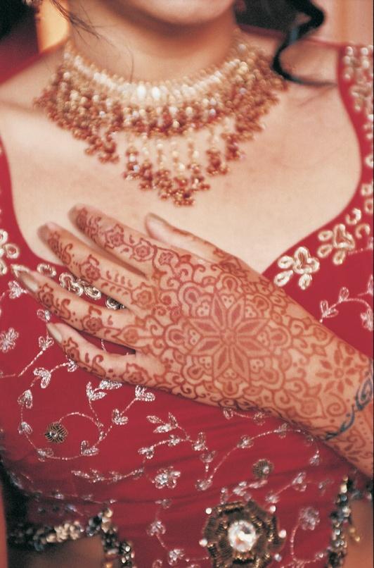 Henna tattoo art on bride's hand over bodice