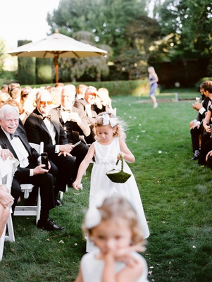 flower girl with white bow and moss basket tossing petals