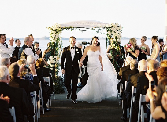 Couple holding hands and walking up pier aisle