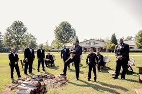 Groom and groomsmen in suits tuxedos on lawn of private estate farm with wood lounge chairs unique