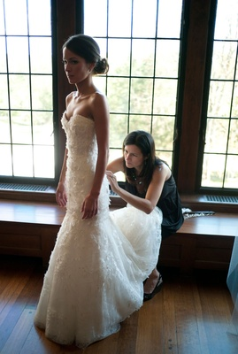 brides mother helps her fix her white wedding dress before her ceremony