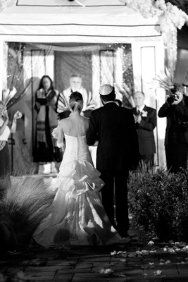 Black and white photo of bride walking up aisle