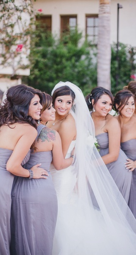 Bride smiling with bridesmaids in purple strapless dresses