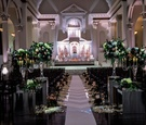 Wedding ceremony at Vibiana altar lighting flower arrangements on risers petals along aisle runner