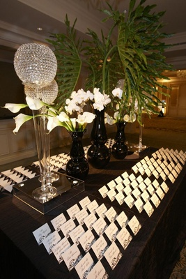 Table with seating cards, crystal orbs, and tropical flowers