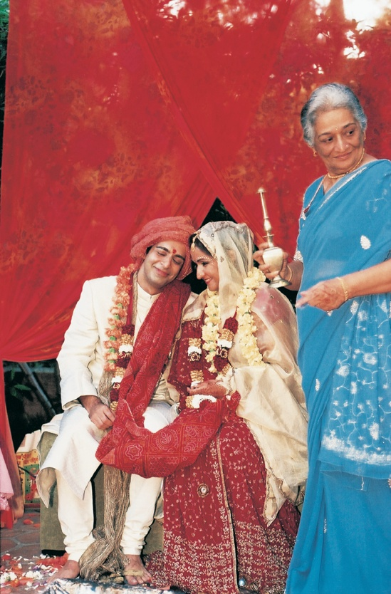 Bride and groom smile on mandap structure
