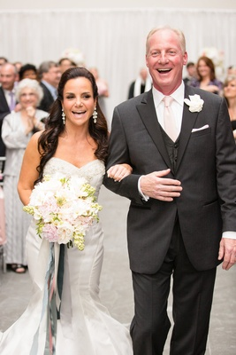 the bride groom smile walking up aisle trumpet wedding gown sweetheart neck charcoal tuxedo pink tie
