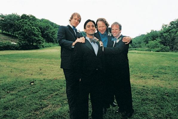 Groomsmen pose outside on grassy lawn