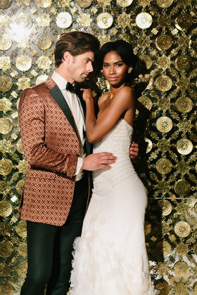 bride in inbal dror mermaid gown, groom in bronze patterned tuxedo jacket, golden wall as backdrop
