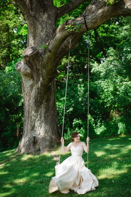Bride on swing hanging from tree at Crossed Keys Inn