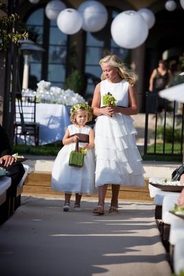 Two flower girls walk down beach wedding aisle