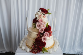 wedding cake adorned with dark burgundy flowers, pink roses, red and white orchids