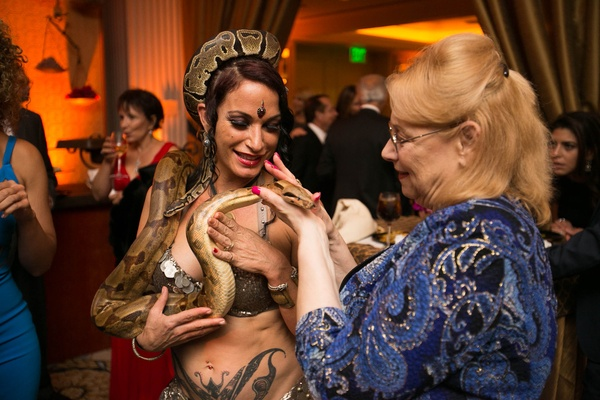 Guest at Moroccan-themed engagement party holds belly dancer's snake
