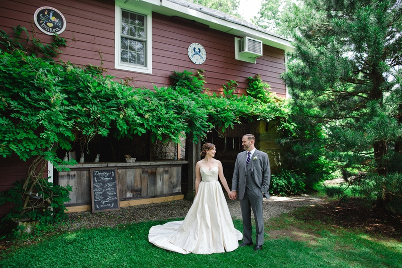 bride in romona keveza legends and groom in brooks brothers in front of crossed keys inn