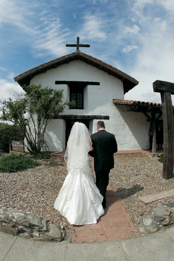 Father of bride walks bride to the entrance of Mission San Francisco Solano