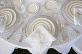 clear chargers with chrome dotted lining, napkin with eyelet detail, geometric linens