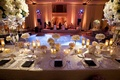 Wedding reception table decorated with tall and low white flower arrangements