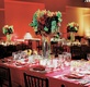 Red wedding reception table with red, green, and orange flower centerpiece