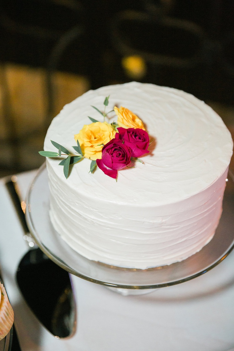 small one-tier white wedding cake featuring foliage and white and pink flowers