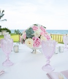Outdoor engagement party tables with pink and white roses, and greenery in silver bowl, pink goblets