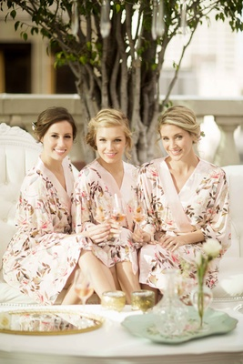 brides and bridesmaids in floral robes drinking champagne