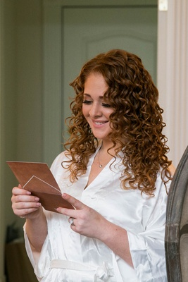 Bride with curly red hair reading note from groom before wedding in white satin robe