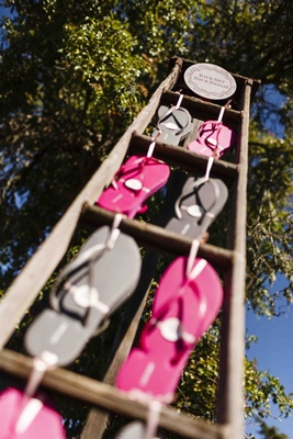 Pink and grey flip flops on rustic ladder at reception
