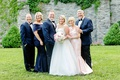 bride and groom with both sets of parents navy blue gown for mother of groom and light pink gown