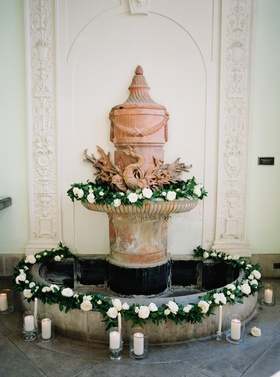 indoor fountain with greenery, roses, and candles for indoor ceremony