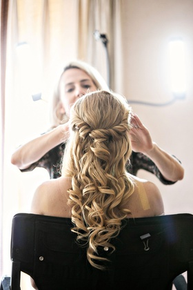 Bride in bridal suite getting ready with professional hair stylist and makeup artist curls half up
