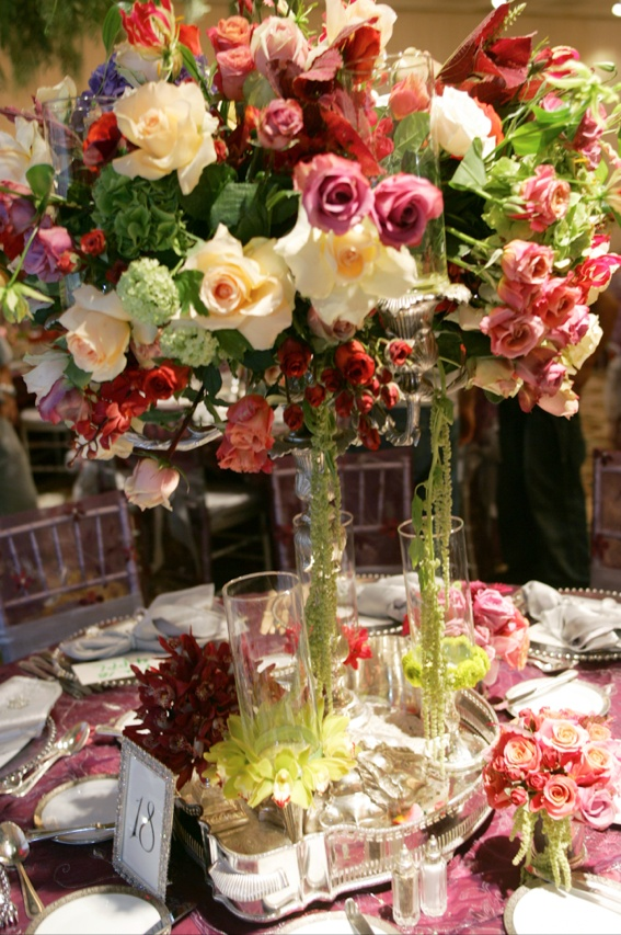 Centerpiece of colorful flowers in a candelabra surrounded by small bouquets