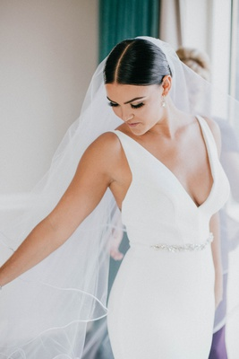 bride in v neck wedding dress jewel belt sash middle part sleek coiffure low bun pretty makeup lash