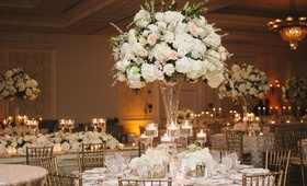 Indoor reception with gold chairs and cream flower arrangements