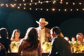 Texan man in cowboy hat standing up at table