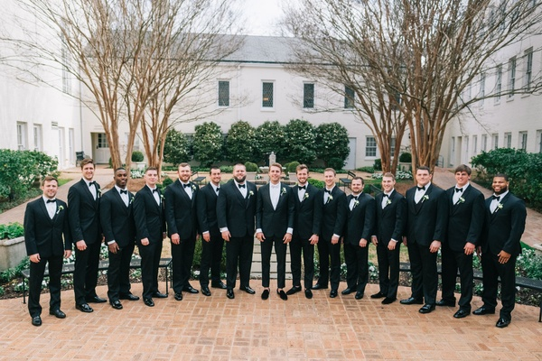 Large wedding party groomsmen in suits and bow ties on brick flooring groom in center with white tie