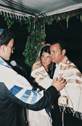 rabbi leads wedding ceremony under chuppah