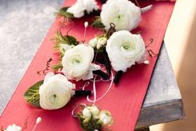 Groomsmen ranunculus blossom wedding boutonniere styles on red cardboard
