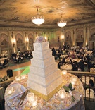 Six-tier wedding cake topped with fresh flowers