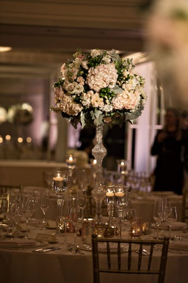 Tall flower arrangement at wedding reception round table floating candles crystal riser hydrangea