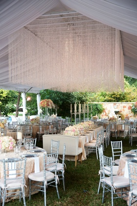 Wedding reception green grass tent crystal installation flowers silver chairs settees candelabra