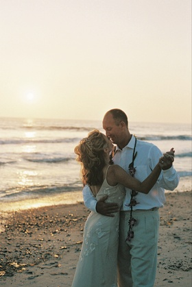 Bride and groom dance together on sand with sunset in background