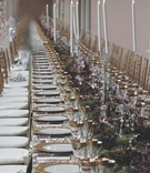 Long reception table topped with gold rimmed china and glassware, runner of flowers, and candelabra