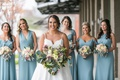 bride in modern trousseau ball gown, spaghetti straps, and pockets, mismatched bridesmaids in blue