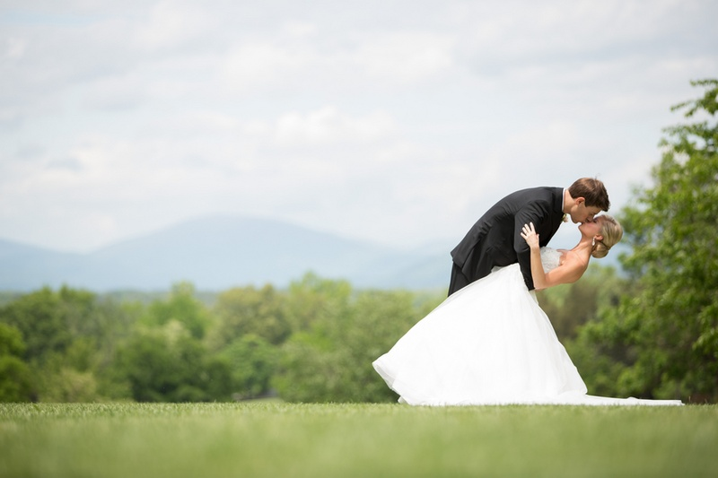 Groom dips bride in ball gown in grass meadow