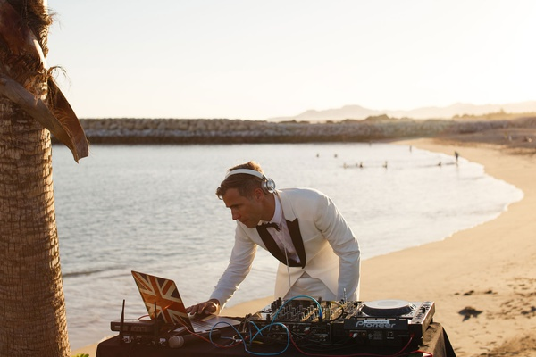 destination wedding dj performing on the beach in a white tuxedo