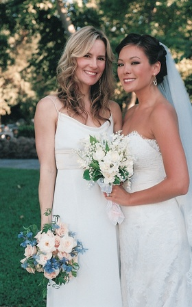 Bridesmaid in white dress with bride outside