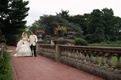 Bride and groom walk through green venue grounds